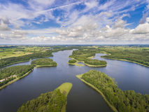 Aerial view of green islands and clouds at summer sunny day.Wydminy lake on Masuria in Poland. stock photos