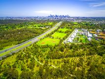Aerial view of green parkland, Melbourne Polytechnic, and Melbourne CBD skyscrapers in the distance on summer day. Aerial view of green parkland, Melbourne Royalty Free Stock Image