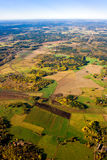 Aerial view of a green rural area in autumn. Aerial view of a green rural area under blue sky in autumn Royalty Free Stock Photos