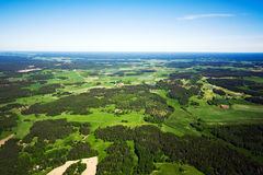 Aerial view of a green rural area under blue sky. Aerial view of green rural landscape under blue sky Stock Photo