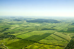 Aerial view of a green rural area under blue sky Stock Photos