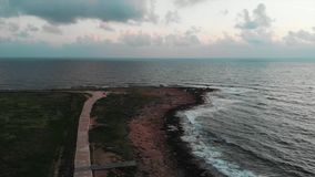 Aerial view of green tourist promenade with rocky beach. Drone shot of people walking along pedestrian path at beautiful sunset stock video footage