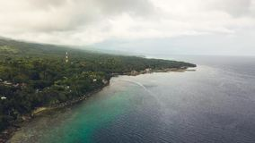 Aerial view green tropical island and turquoise sea on cloudy sky background. Beautiful landscape from above flying stock video footage