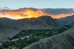 Aerial view of green valley in between high deserted mountains during sunset Stock Photo