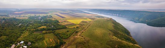 Aerial view on green and yellow parts of fields in autumn season. Panorama of big river canyon, village and rural fields on hills. Aerial view on green and royalty free stock image