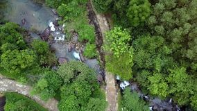 Aerial View Ground Road Meandering along River with Cascades. Aerial view dirty ground road meandering along fast mountain river with cascades among tropical stock video