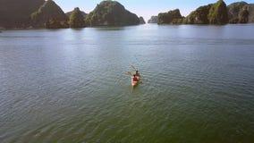 Aerial View Guy Girl Row Kayak on Ocean Bay Rippling Water. Aerial view guy girl row kayak with paddles on azure ocean bay rippling water surface against old stock video