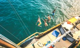 Aerial view of happy millenial friends jumping from sailboat on sea ocean trip - Rich guys and girls having fun together in royalty free stock photo
