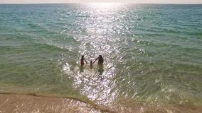AERIAL VIEW. Happy Mother With Two Children Running Into The Sea stock video