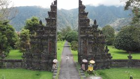 Aerial view of happy tourist woman with drone running through bali traditional gate in bedugul Traditional Balinese