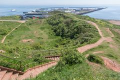 Aerial view harbor seen from cliffs of German island Helgoland. In front stairs down to the village stock photos