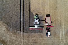 Harvester working on the field and filling the truck. Aerial view on the harvester working on the field and filling the truck Royalty Free Stock Photo