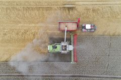 Harvester working on the field and filling the truck. Aerial view on the harvester working on the field and filling the truck Royalty Free Stock Photos