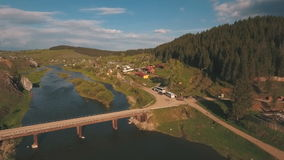 Aerial view from a height on the river and village near a forest stock footage