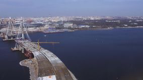Aerial view from helicopter fly above water. Bridge under construction. River. Sunny day. Cityscape. Height stock footage