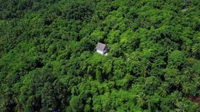Aerial view of hermitic house standing apart in remote isolated location among tropical forest. Shot with a DJI Mavic fps29,97 4k stock footage