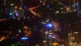 Aerial view of high-rise buildings & urban traffic at night,China,timelapse. Elevated view of urban traffic & brightly lit high-rise buildings at night in stock video footage