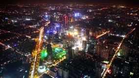Aerial view of high-rise buildings & urban traffic at night,China,timelapse. Elevated view of urban traffic & brightly lit high-rise buildings at night in stock footage