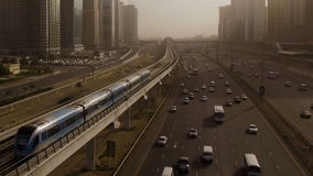 Aerial view of high-speed trains blue, which travels through the overpass along the highway with cars surrounded by stock video footage