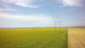 Aerial view of High-voltage power transmission towers over green. Farm fields Stock Image