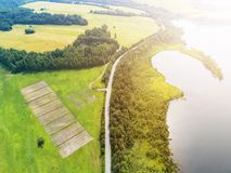 Aerial view of highway. Aerial view of a country road near the lake. Car passing by. Aerial road. Aerial view flying. Captured fro. M above with a drone. Soft stock image