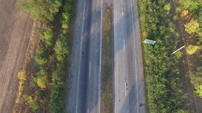 Aerial view a highway in both directions with moving cars. Aerial view the highway of two lane direction and road signs and markings, with moving cars, on both stock footage