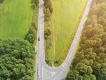 Aerial view of highway with car. Aerial view of a country road with moving car. Car passing by. Aerial road. Aerial view flying. Captured from above with a Royalty Free Stock Image