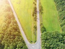 Aerial view of highway with car. Aerial view of a country road with moving car. Car passing by. Aerial road. Aerial view flying. Captured from above with a Stock Photos