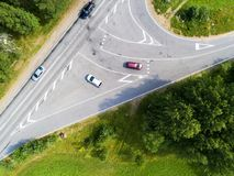 Aerial view of highway with car. Aerial view of a country road with moving car. Car passing by. Aerial road. Aerial view flying. C. Aptured from above with a Stock Image