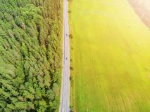 Aerial view of highway with car. Aerial view of a country road with moving car. Car passing by. Aerial road. Aerial view flying. C. Aptured from above with a stock photo