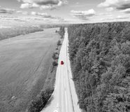 Aerial view of highway. Aerial view of a country road with moving red car. Car passing by. Aerial road. Aerial view flying. Captur. Ed from above with a drone royalty free stock photo