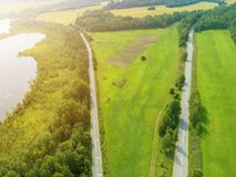 Aerial view of highway. Aerial view of a country road near the lake. Car passing by. Aerial road. Aerial view flying. Captured fro. M above with a drone. Soft stock images