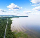 Aerial view of highway. Aerial view of a country road near the lake. Car passing by. Aerial road. Aerial view flying. Captured fro. M above with a drone. Soft stock photo