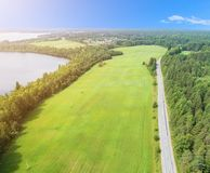 Aerial view of highway. Aerial view of a country road near the lake. Car passing by. Aerial road. Aerial view flying. Captured fro. M above with a drone. Soft stock photos