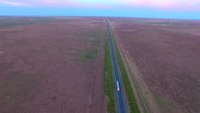 Aerial view highway road on dusk semi-trailer. Aerial scene of outback highway or open road on dusk sunset with truck lorry Semi-trailer traveling on rural stock video