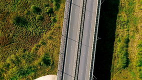 Aerial view highway road in green field. Cars driving on suburban road. Highway landscape view. Top view cars and cargo truck moving on highway. Cars driving stock footage