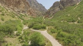 Aerial view of a hiking trail in a canyon in the high desert mountains. Aerial view of a hiking trail and dry river bed in the Rocky Mountains. Rugged train stock footage