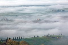 Aerial view of hilltop farmhouses & cypress trees in Tuscany on a foggy spring morning ~ Stock Image