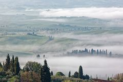 Aerial view of hilltop farmhouses & cypress trees in Tuscany on a foggy spring morning ~. Amazing scenery of Tuscany countryside with rolling hills veiled in Stock Photos