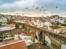 Aerial view of historic Evora in Alentejo, Portugal. Aerial view of historic Evora with Roman aqueduct and birds, Alentejo, Portugal Royalty Free Stock Images