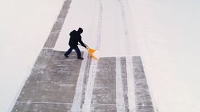 Aerial view of homeowner shoveling show from driveway. An aerial view of a homeowner shoveling snow from the driveway at a home in a typical Pennsylvania stock video