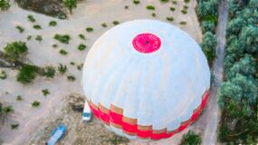 Aerial view of a hot-air balloon in Cappadocia, from above onto the balloon shortly after take-off