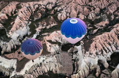 Aerial view of hot air balloons flying over rocky landscape. Stock Photo