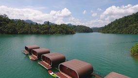 Aerial View on Houses at Cheow Lan Lake, Khao Sok National Park in southern Thailand. HD Slowmotion. Aerial View on Houses at Cheow Lan Lake, Khao Sok National stock video footage