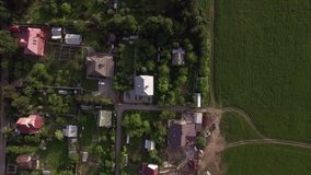 Aerial view of houses with green yards in countryside, Russia. Flying over the cottages with green yards in Russian countryside stock video footage