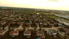 Aerial view houses in residential suburban neighborhood with backyard landscape and rooftops