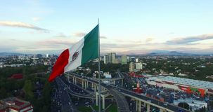 Drone-Aerial view of a huge mexican flag waving. In the back, panoramic viw of Mexico City. Many cars transit for the avenue. stock footage