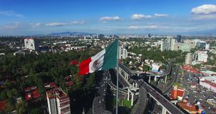 Drone-aerial view of a huge mexican flag waving. In the back, panoramic view of Mexico City. Many cars transit for the avenue. stock footage