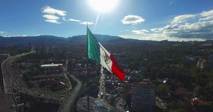 Drone-Aerial view of a huge mexican flag waving, the sun is up the flag. In the back, panoramic view of some suburbs and mountains stock footage