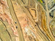 Aerial view of big trucks in huge, open pit mine. Aerial view of huge, modern open pit mine in Minas de Riotinto, Andalusia, Spain Royalty Free Stock Photography